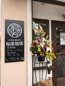 桜座珈琲の看板と入り口のドアが写っている写真